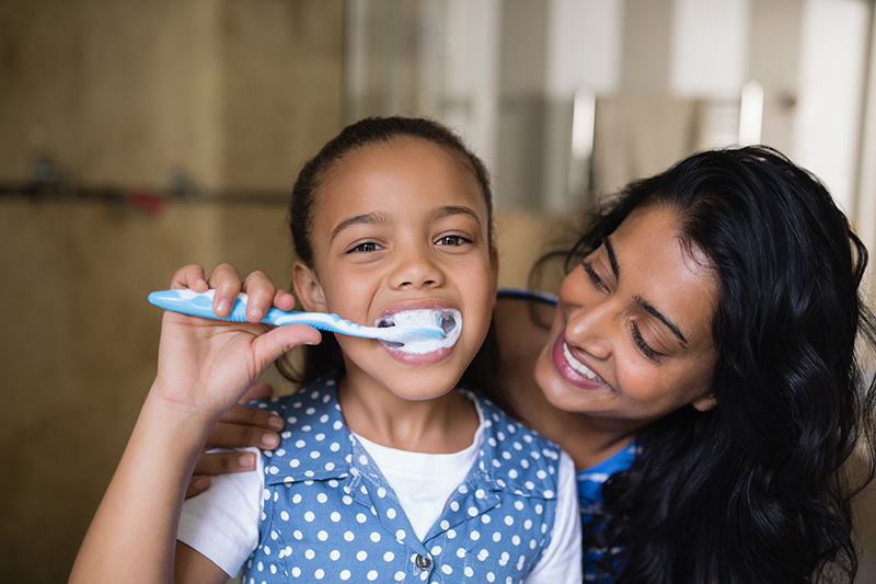 girl brushing teeth with mother